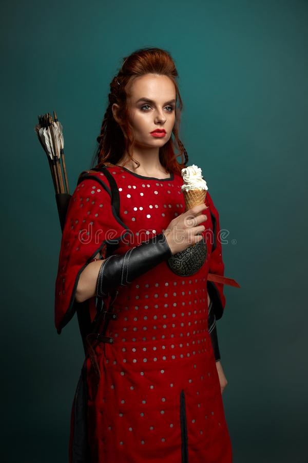 Beautiful woman in medieval costume holding ice cream. Gorgeous model with red lips and ginger hair posing, holding tasty, white ice cream. Beautiful woman stock photos