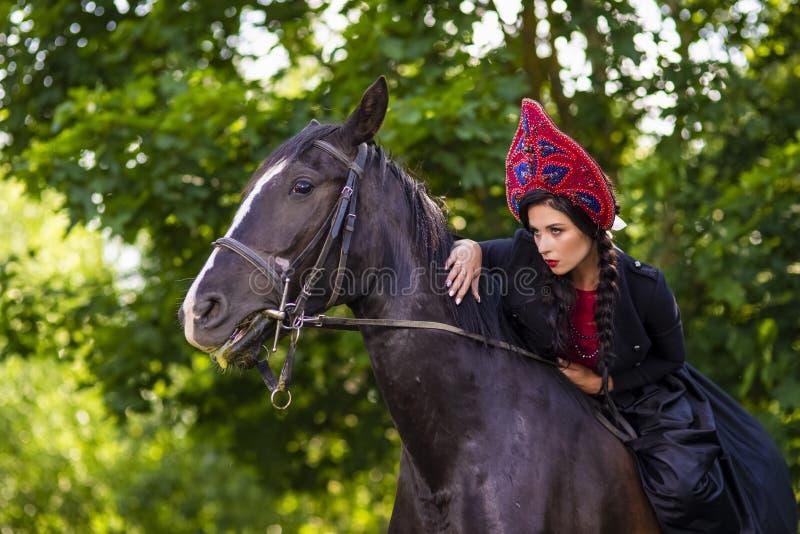 Gorgeous Model in Russian Style Kokoshnik Straddling On the Thoroughbred Horse. Posing Against Nature Background. Horizontal Image Orientation royalty free stock image