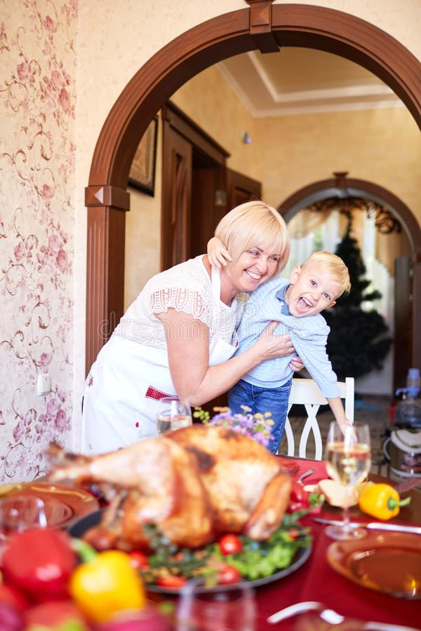 Grandmother and little boy having fun on Thanksgiving on a blurred background. Family holidays concept. Gorgeous modern grandmother having fun with a funny stock image