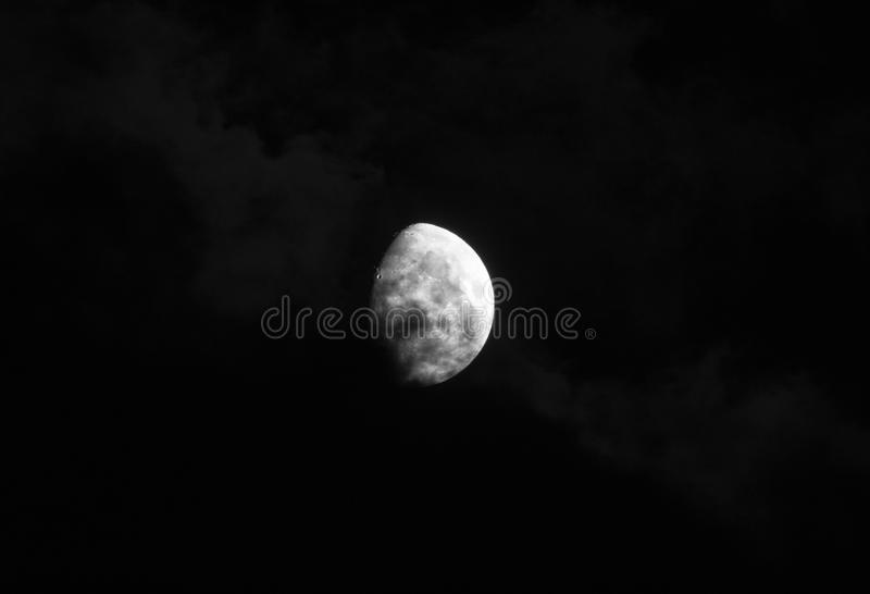 Gorgeous moon in a dark blue night sky gets covered by soft wispy dark clouds royalty free stock photo