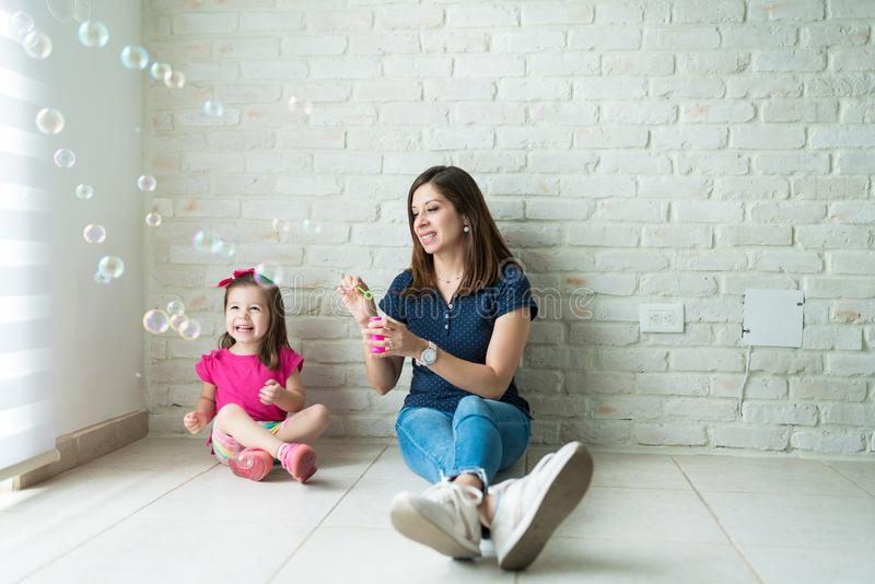 Playful Woman And Girl Having Fun With Bubbles At Home stock image