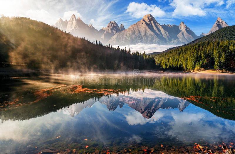 Gorgeous mountain lake in autumn fog. Gorgeous composite mountain lake in autumn fog. lovely nature scenery with coniferous forest, rocky peaks and beautiful sky stock images