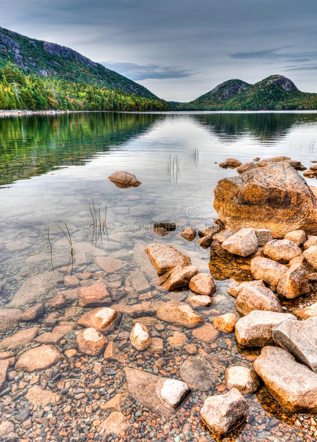 Gorgeous mountain lake with woodlands reflection and red rocks in the foreground stock images