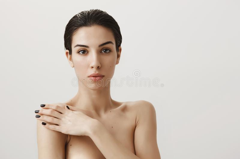 Gorgeous naked woman with piercing showing her natural beauty while standing nude over gray background, covering body. With hand, expressing sensuality and royalty free stock images