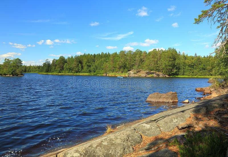 Gorgeous nature landscape view of lake with rocky coast line and green tall trees on blue sky background. Sweden, Europe. Beautiful backgrounds stock photos