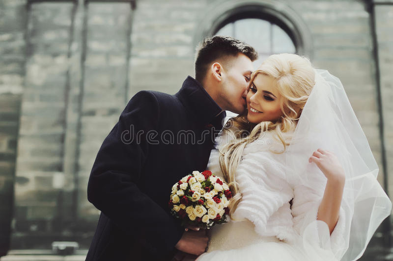 Gorgeous newlywed bride in white coat and handsome groom valentynes kissing in front of old baroque church closeup royalty free stock photos