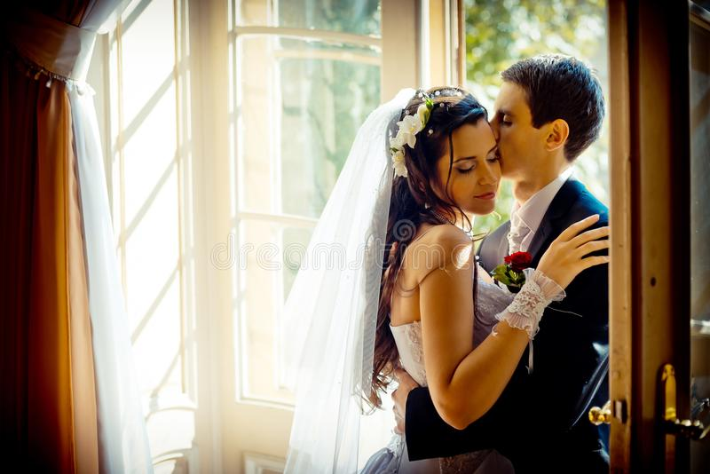 The gorgeous newlywed couple is tenderly hugging near the old open window. The handsome groom is softly kissing his stock photography