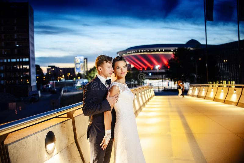 Gorgeous newlyweds on the city bridge at night royalty free stock photography