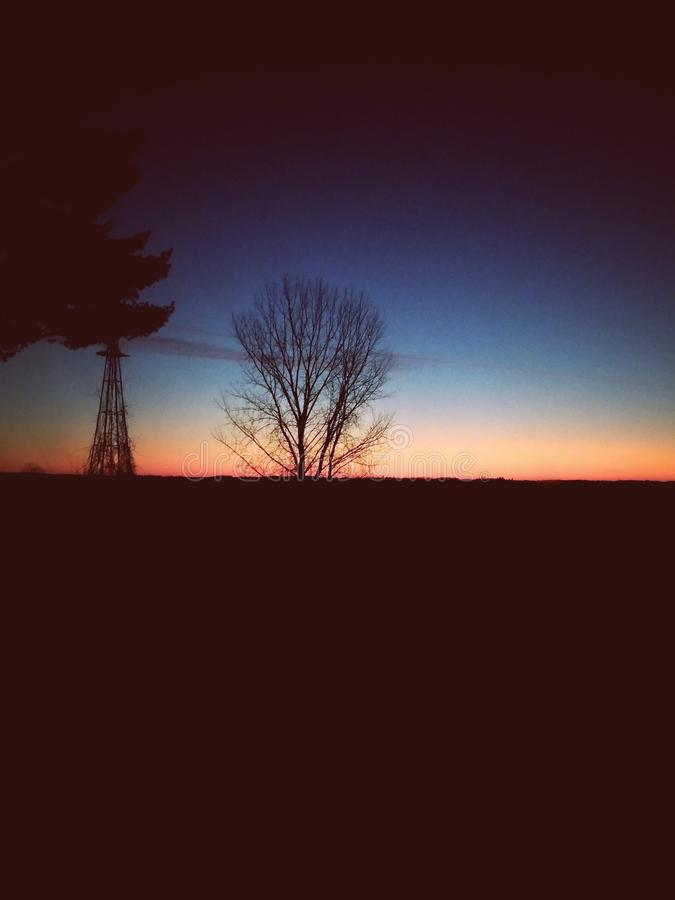 Gorgeous. One of my favorite sunset pictures with an old windmill and trees stock images