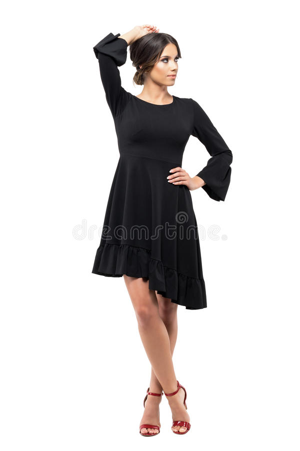 Gorgeous passionate vogue Latin woman in black dress posing and looking away. Full body length portrait isolated on white background royalty free stock photography