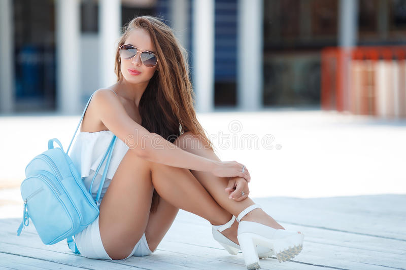 Gorgeous portrait of a young woman outdoors. Young beautiful brunette woman with brown long hair, sun glasses, pink lipstick, attractive birthmark near his royalty free stock photography