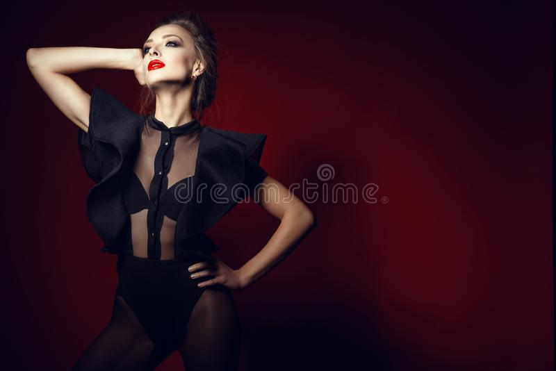 Gorgeous posh lady with updo hair and perfect make up wearing semi transparent lace bodysuit with frill sleeves looking up stock photos
