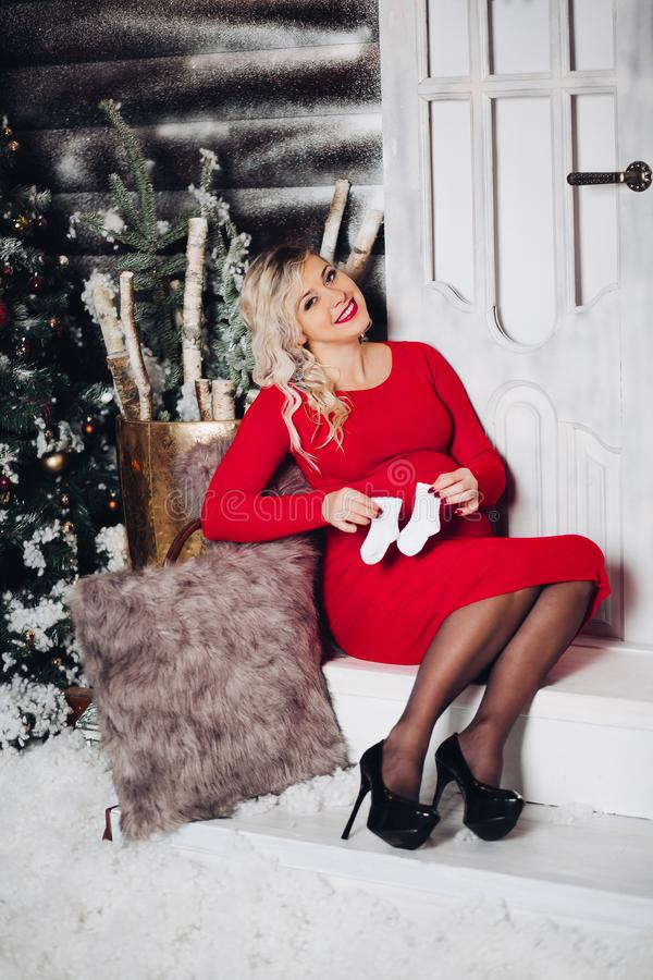 Gorgeous pregancy woman in red holding socks on stomach. Christmas. royalty free stock images