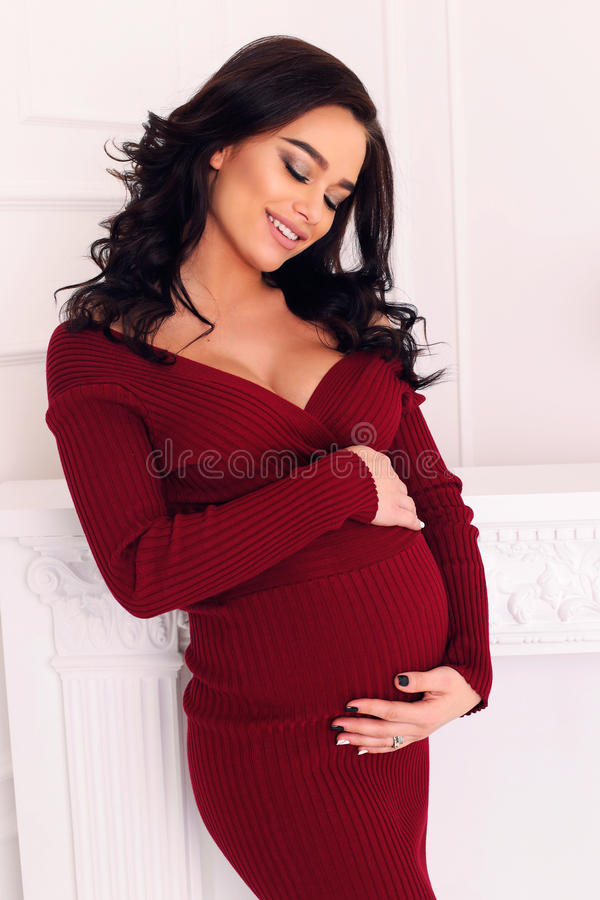 Gorgeous pregnant woman with long dark hair posing at bedroom royalty free stock images