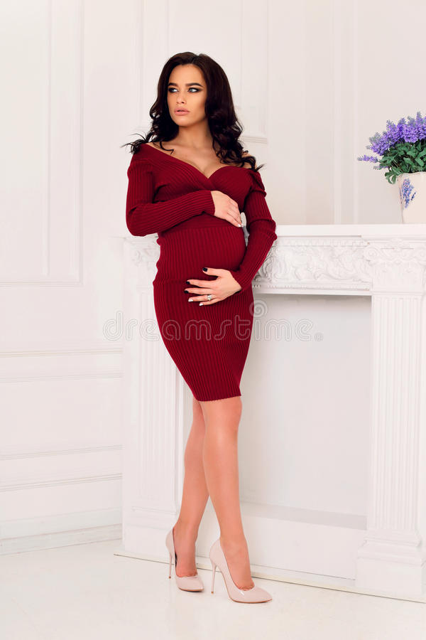 Gorgeous pregnant woman with long dark hair posing at bedroom. Fashion interior photo of gorgeous pregnant woman with long dark hair in elegant red dress posing royalty free stock photo