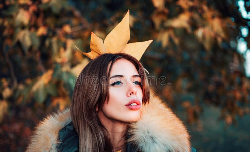 Gorgeous pretty woman in furry coat fallen leaf on head as crown. Trendy outfit. Her confidence is stunning. Woman stock photography