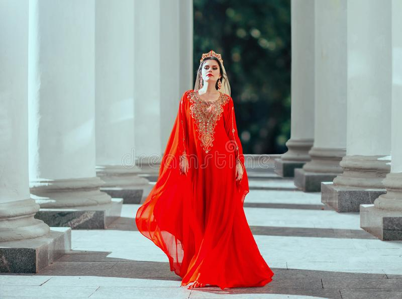 Gorgeous proud dark-haired confident haseki queen roksolana in amazing expensive luxury red long flying dress with. Gold, beads and precious stones, wearing stock images