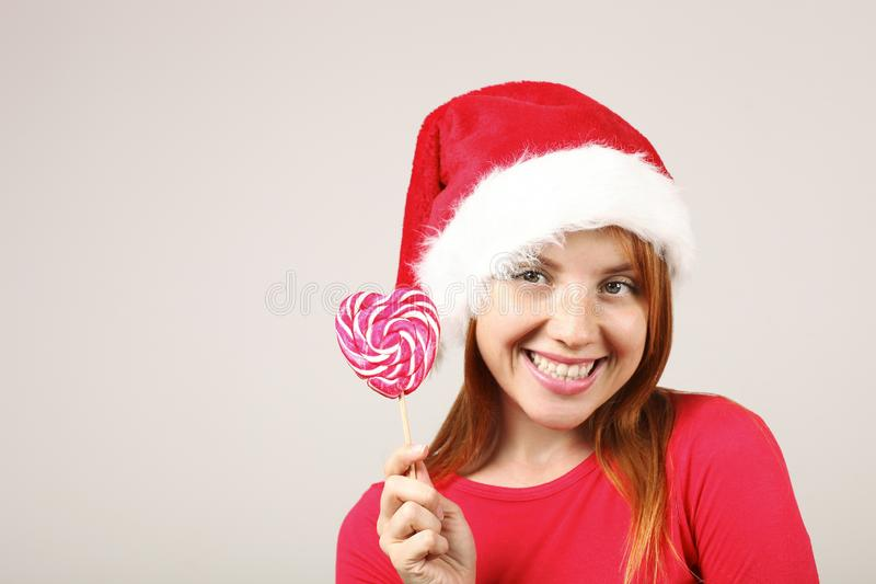 Gorgeous redhead female wearing Santa`s hat with pop-pom, celebrating winter festive season holidays. stock photos