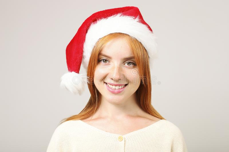 Gorgeous redhead female wearing Santa`s hat with pop-pom, celebrating winter festive season holidays. royalty free stock image