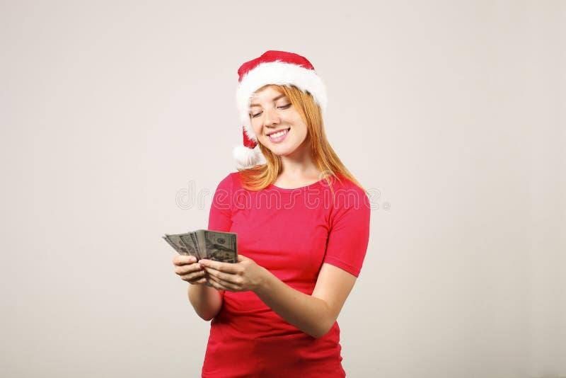 Gorgeous redhead female wearing Santa`s hat with pop-pom, celebrating winter festive season holidays. royalty free stock photos