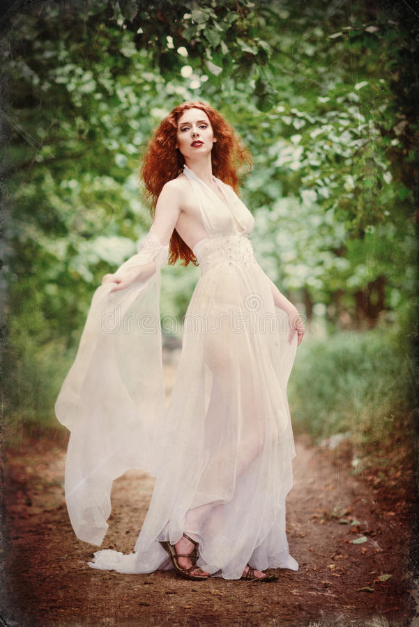 Gorgeous redhead woman wearing white dress in a forest. Grunge texture effect stock image