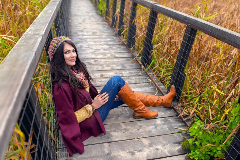 A gorgeous romantic young woman with beautiful long brown hair, sitting on a wooden bridge, in nice autumn outfit stock photo