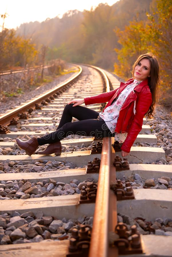 A gorgeous romantic young woman seated down on the railroad tracks, smiling and looking at the camera, in fall scenery royalty free stock photo