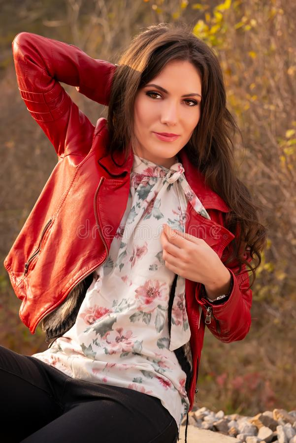 A gorgeous romantic young woman smiling and looking at the camera, in fall scenery outdoors, seated down. Fashion stock images