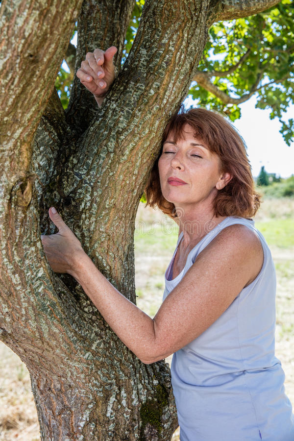 Gorgeous 50s woman in harmony with nature and environment. Middle aged wellness - gorgeous 50s woman embracing a tree in harmony with nature for symbol of stock photos
