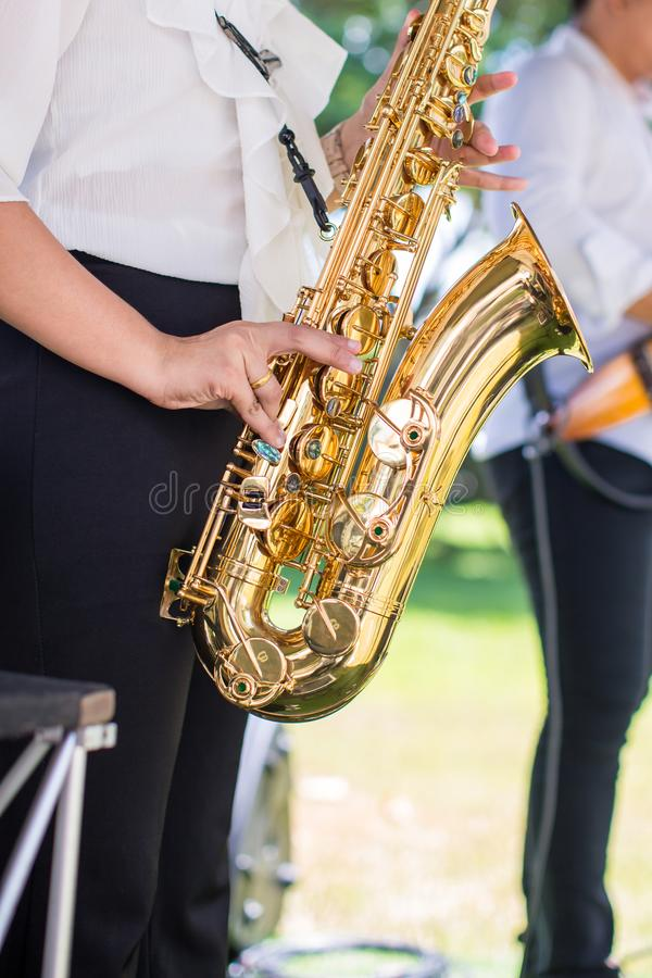 Gorgeous saxophonist lady is playing saxophone in wedding ceremony. musician woman. attractive woman and music instrument . royalty free stock images