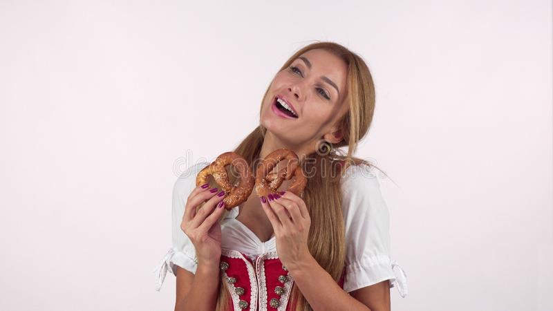 Gorgeous german woman in Oktoberfest dress looking excited holding pretzels. Lovely young Bavarian waitress enjoying beer festival. Food and drink, holidays stock image