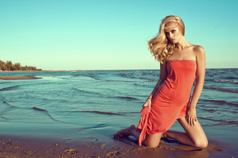 Gorgeous slim blond model in coral red strapless dress standing on knees in the sea water and looking aside royalty free stock image
