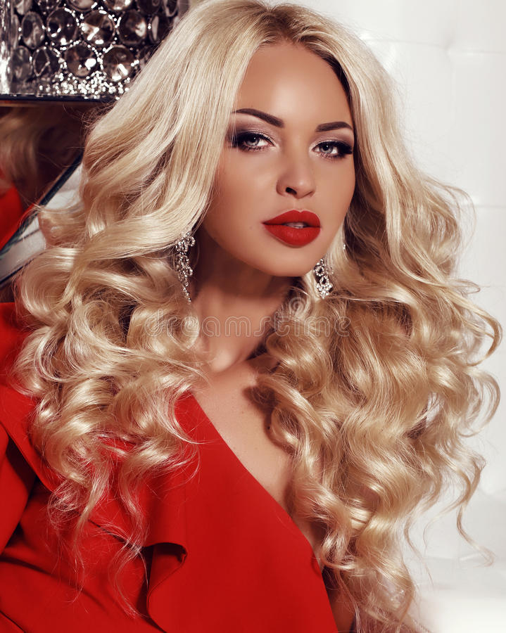 Gorgeous woman with blond hair wears luxurious red dress and bijou. Fashion interior photo of gorgeous woman with long blond hair wears luxurious red dress and stock photo