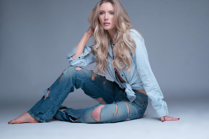 Gorgeous slender blond woman in designer jeans stock images