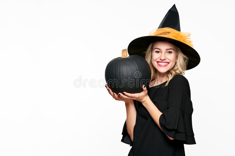 Gorgeous smiling Halloween Witch holding large black pumpkin. Portrait of a beautiful young woman wearing witch hat. Halloween. royalty free stock images