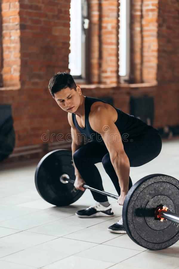 Gorgeous strong guy performing lifting. In the contest. full length photo. side view shot.fitness stock photos