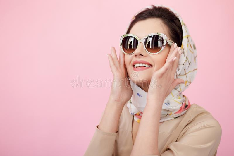 Gorgeous style of a young woman dressed elegant clothing, posing sensual in studio, isolated on a pink background. stock photography