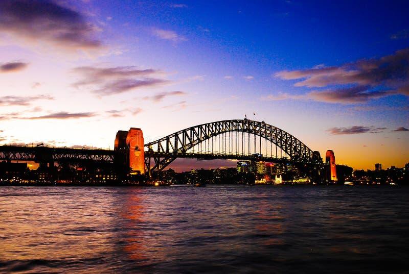 Gorgeous sunset on mighty steel Sydney Harbor bridge crossing the ocean royalty free stock image