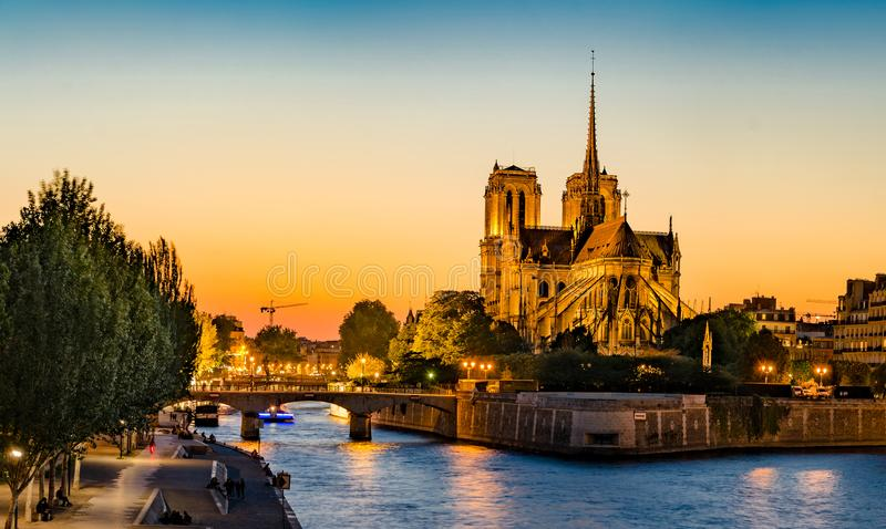 Gorgeous sunset over Notre Dame cathedral with puffy clouds stock image