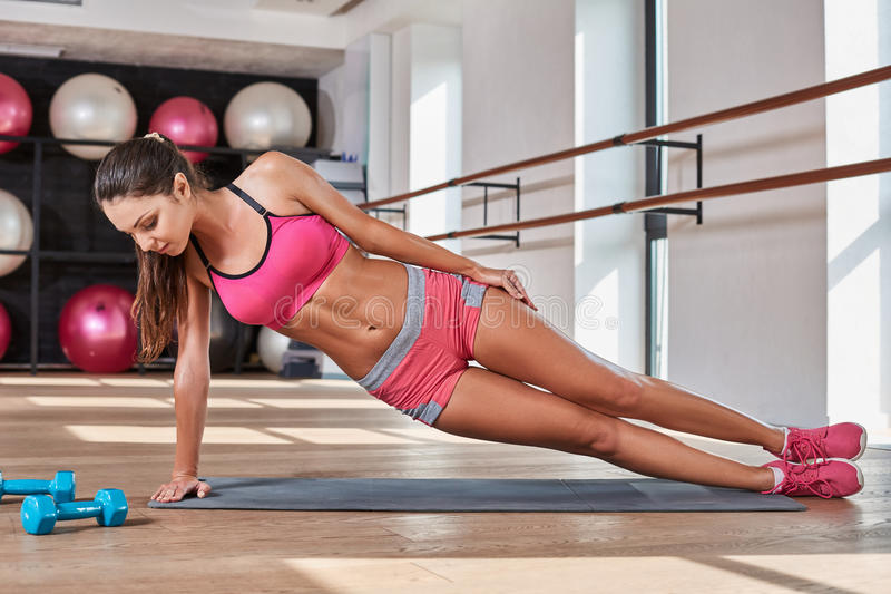 Gorgeous suntanned brunette doing exercises. Perfect plank. Full-length side view of young beautiful woman in sportswear doing plank while standing in front of stock image