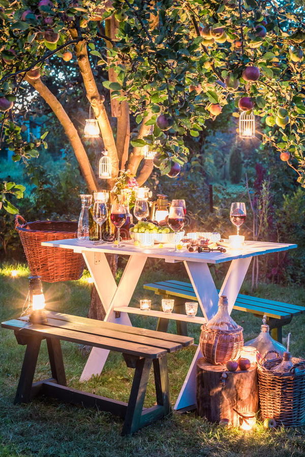 Gorgeous table full of wine and fruits in garden at dusk. In summer royalty free stock image
