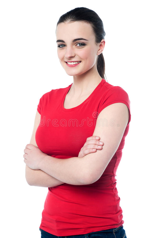 Gorgeous teen girl posing, arms crossed. Cheerful pretty girl in casuals posing with folded arms stock images