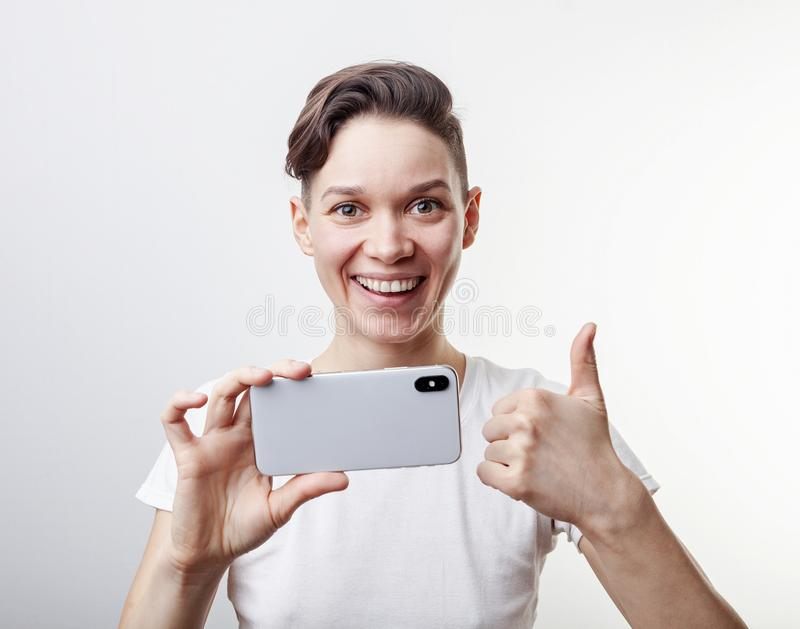 Gorgeous teenage girl is taking a photo using front camera in her smartphone and showing thumb up. Isolated on white background royalty free stock photo