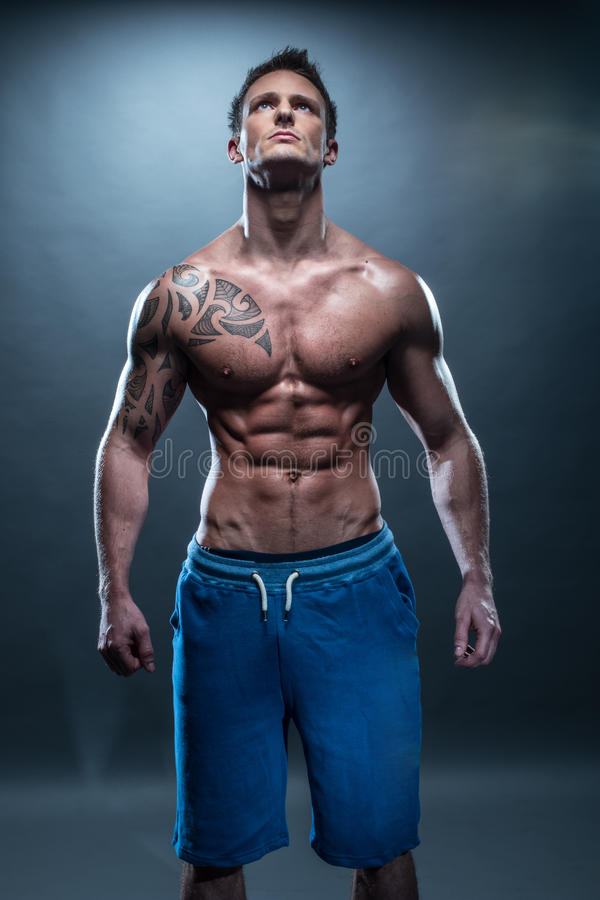 Gorgeous Topless Young Muscular Man Looking Up. Portrait of a Gorgeous Topless Muscular Man with Tattoo, Showing his Healthy Fit Body While Looking Up on an royalty free stock photo