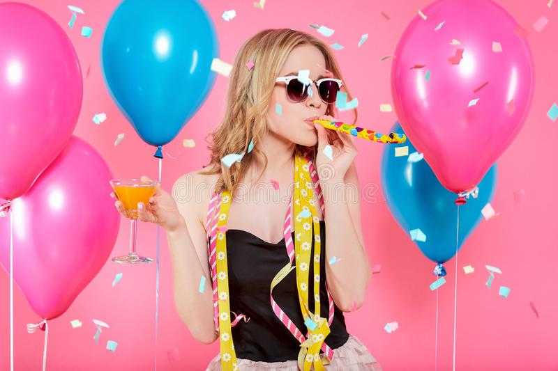 Gorgeous trendy young woman in party outfit celebrating birthday. Party mood, balloons, flying confetti, cocktail and dancing. Gorgeous trendy young woman in stock image