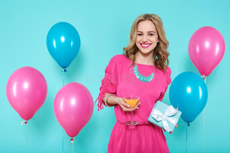 Gorgeous trendy young woman in party outfit holding cocktail and a gift box. Birthday Party concept. royalty free stock images