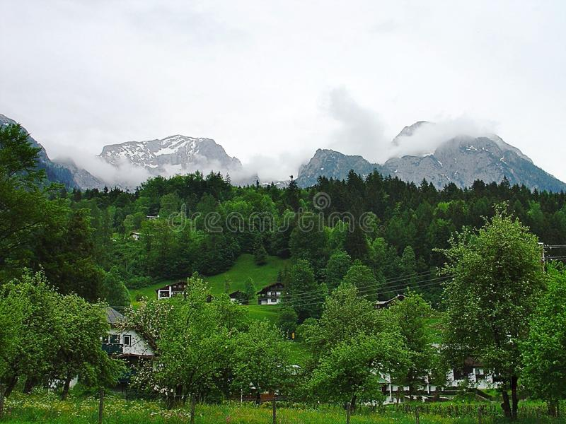 Gorgeous view of houses in Alps mountains. Bavaria. Germany. Europe. Green trees and snow on top of mountains. Amazing nature landscape background stock image
