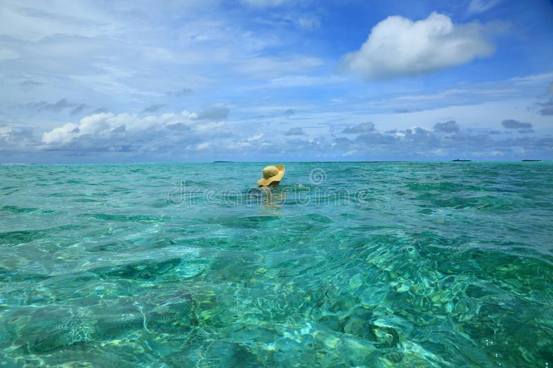 Gorgeous view of Indian Ocean, Maldives. Woman in hat swimming. Turquoise water surface and blue sky with white clouds. Beautiful royalty free stock photography
