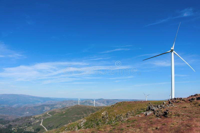 Gorgeous view of rocky mountain landscape with wind turbines in the distance. Beautiful clear blue sky. Aveiro, Portugal royalty free stock image