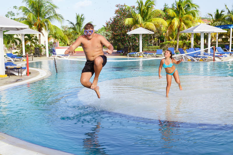 gorgeous view of teenage boy and little girl jumping, playing in tropical outdoor swimming pool royalty free stock images